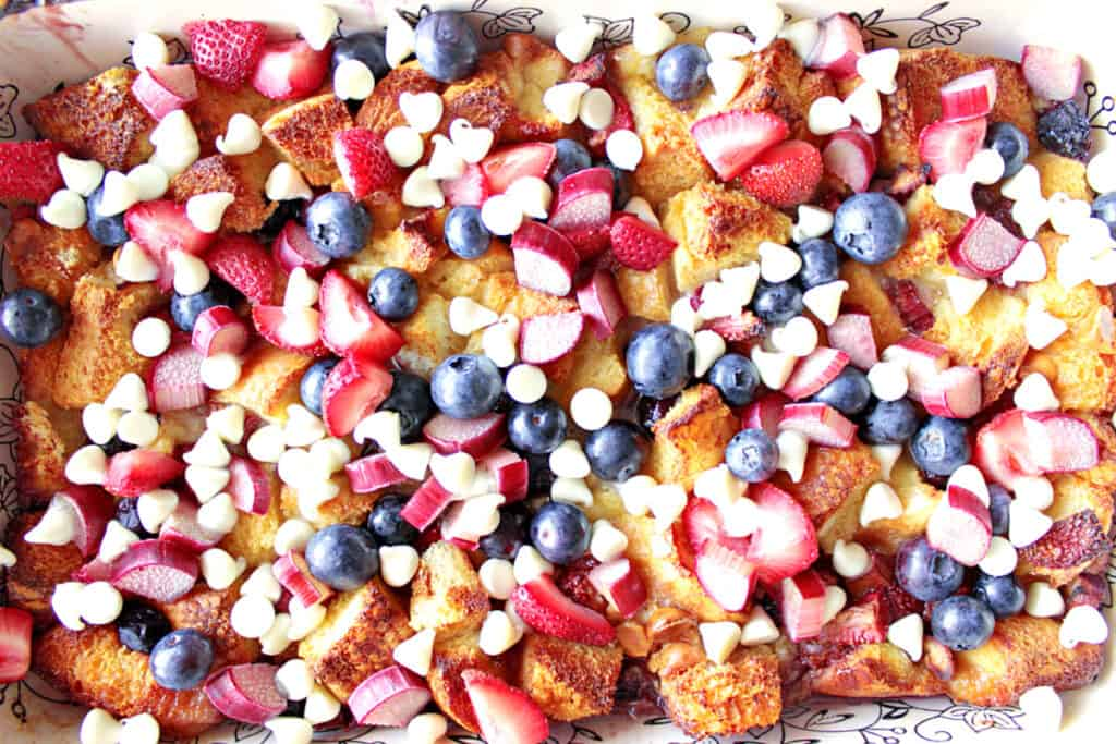 A direct overhead photo of Red, White, and Blue Bread Pudding with brown bread, strawberries, rhubarb, and white chocolate.
