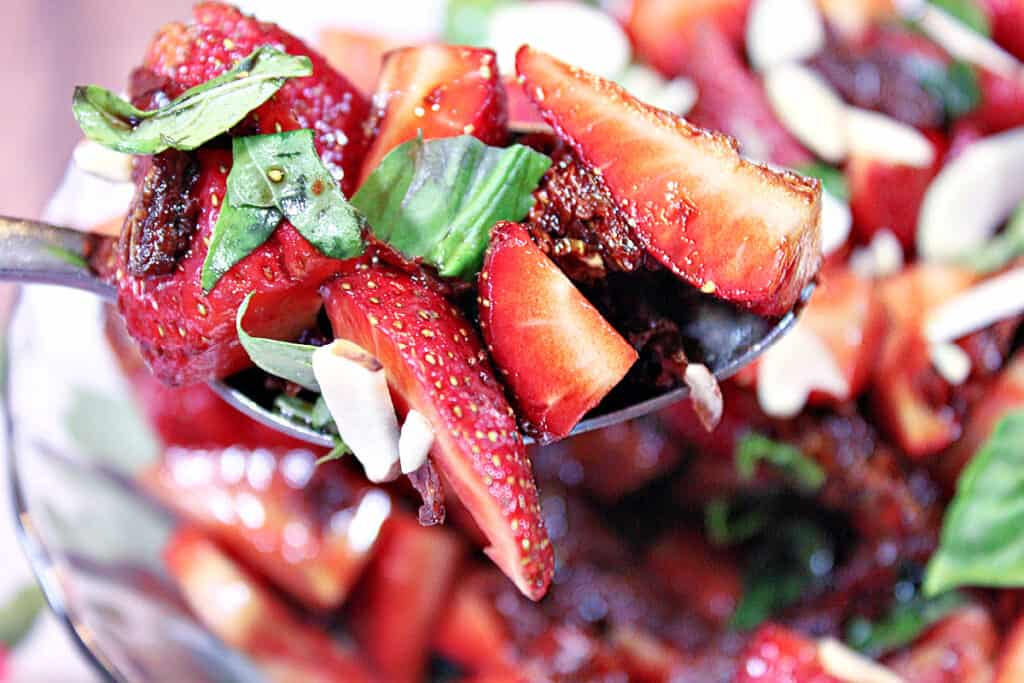 A horizontal photo of a spoon filled with Strawberry Basil Salad with almonds.