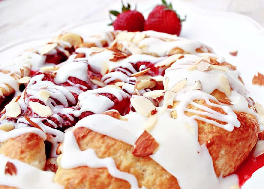 A super closeup horizontal image of a homemade Strawberry Crostata with a white sugar glaze and fresh strawberries as a garnish.