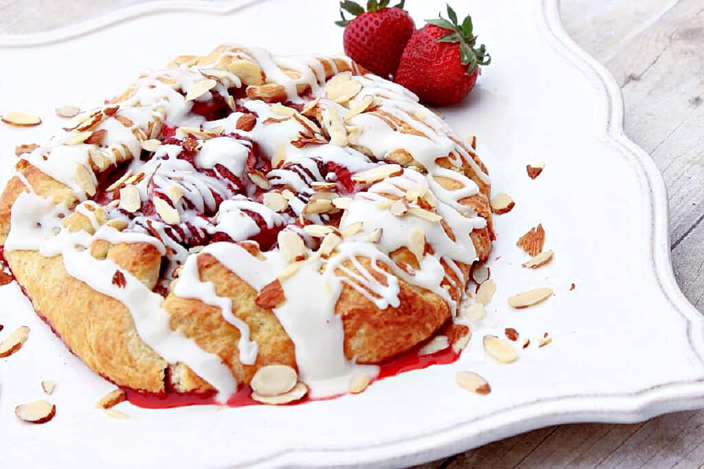 An offset horizontal photo of a Strawberry Crostata on a pretty square white plate with fresh strawberries as garnish.