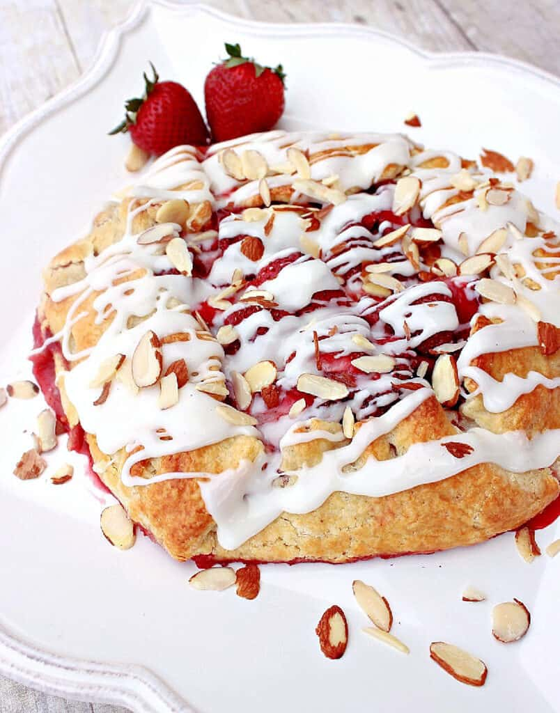 A vertical closeup image of a Strawberry Crostata with a glaze and sliced almonds over top.