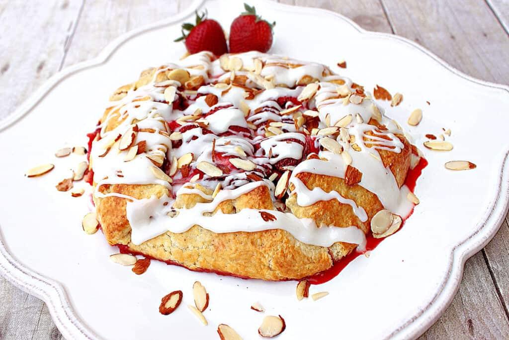 A Strawberry Crostata on a pretty white square plate with a almond glaze and sliced almonds.
