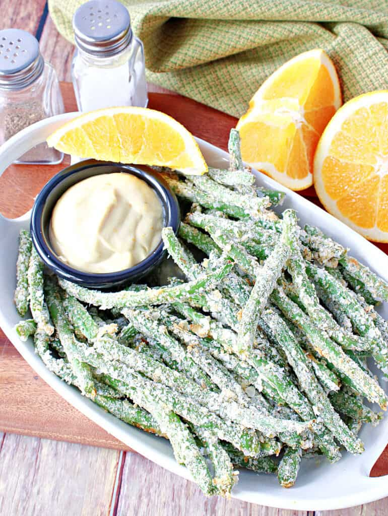 A vertical overhead closeup of a bowl of Everything Green Bean Fries along with a small round dish of Orange Honey Dipping Sauce and fresh oranges.