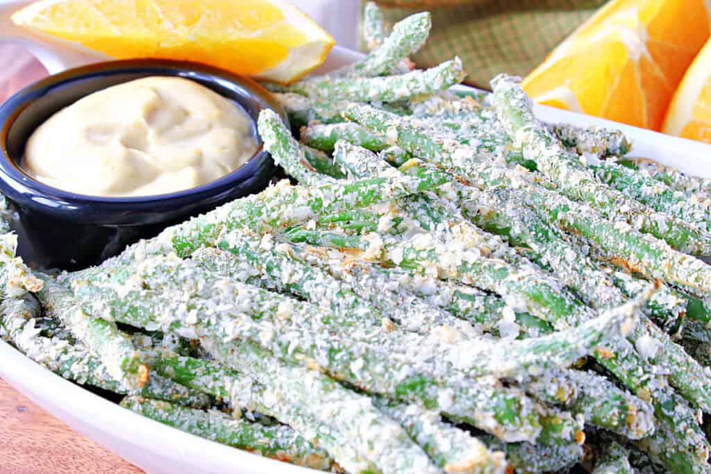 A horizontal closeup photo of a bowl filled with Everything Green Bean Fries covered in instant potato flakes along with an orange honey dipping sauce.