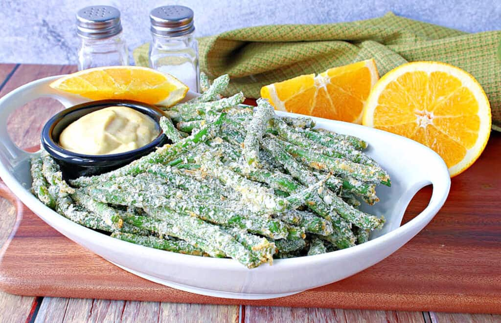 A white oval bowl filled with Everything Green Bean Fries along with an orange dipping sauce and fresh oranges.