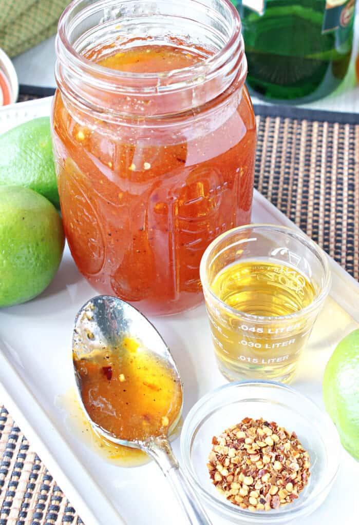 A mason jar, a spoon, and a shot glass along with Irish Whisky Glaze and some limes.