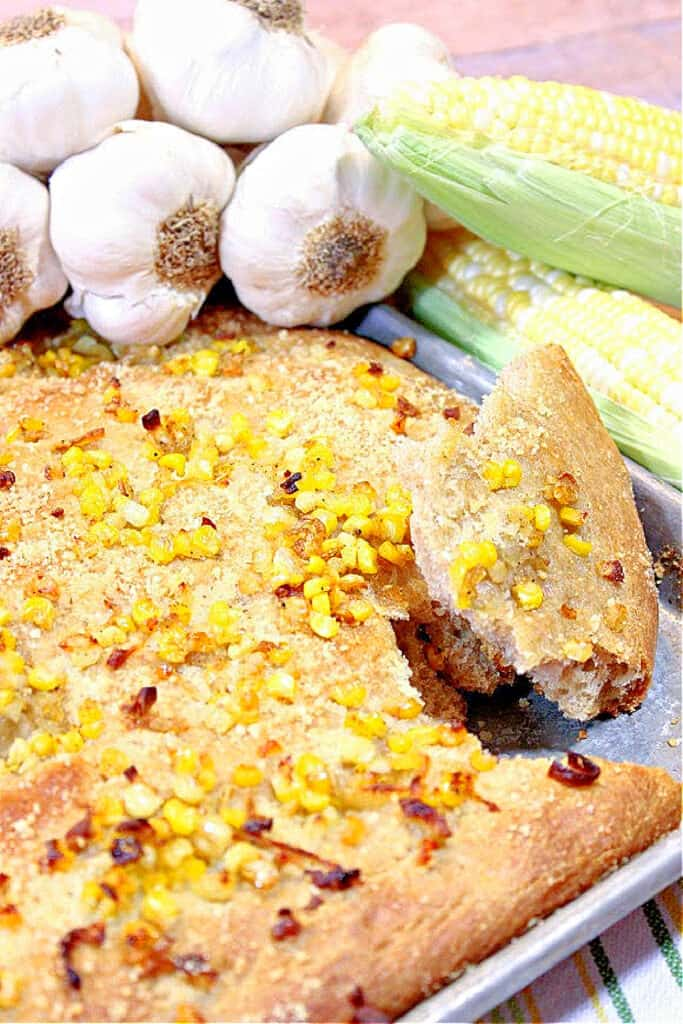 A vertical closeup of a Garlic Focaccia with Sweet Corn on a sheet tray topped with corn, shallots with garlic and corn in the background.