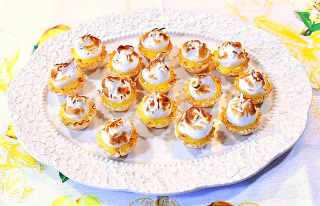 An overhead horizontal photo of a platter of Lemon Meringue Tartlets along with a lemon patterned napkin.