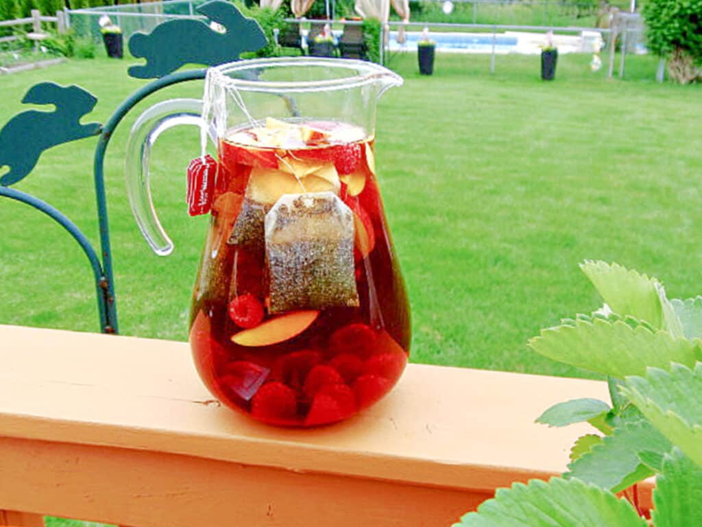 A horizontal photo of a pitcher of Peach and Raspberry Sun Tea steeping in the sunshine on a deck railing.