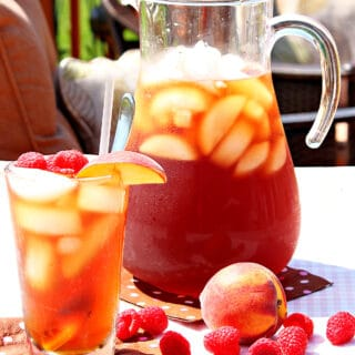 A pitcher and a glass of Peach and Raspberry Sun Tea outside with ice.