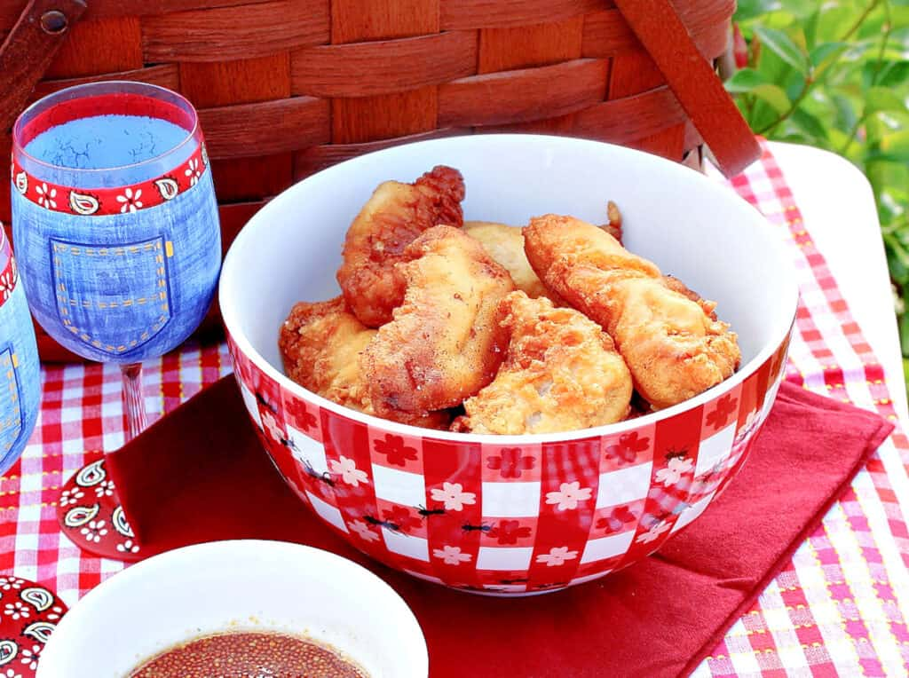 A closeup horizontal photo of a red and white bowl filled with Waffle Batter Fried Chicken Tenders outside on a picnic table.