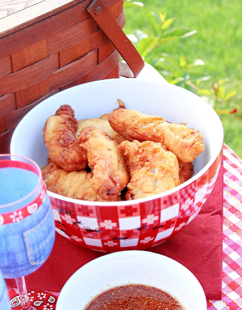 A vertical photo of a red and white checked bowl filled with Waffle Batter Fried Chicken tenders with a picnic basket in the background along with a glass of wine.