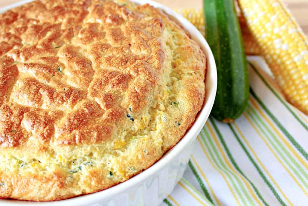 An offset horizontal photo of a Zucchini and Sweet Corn Soufflé in a white casserole dish with a zucchini and sweet corn in the background.