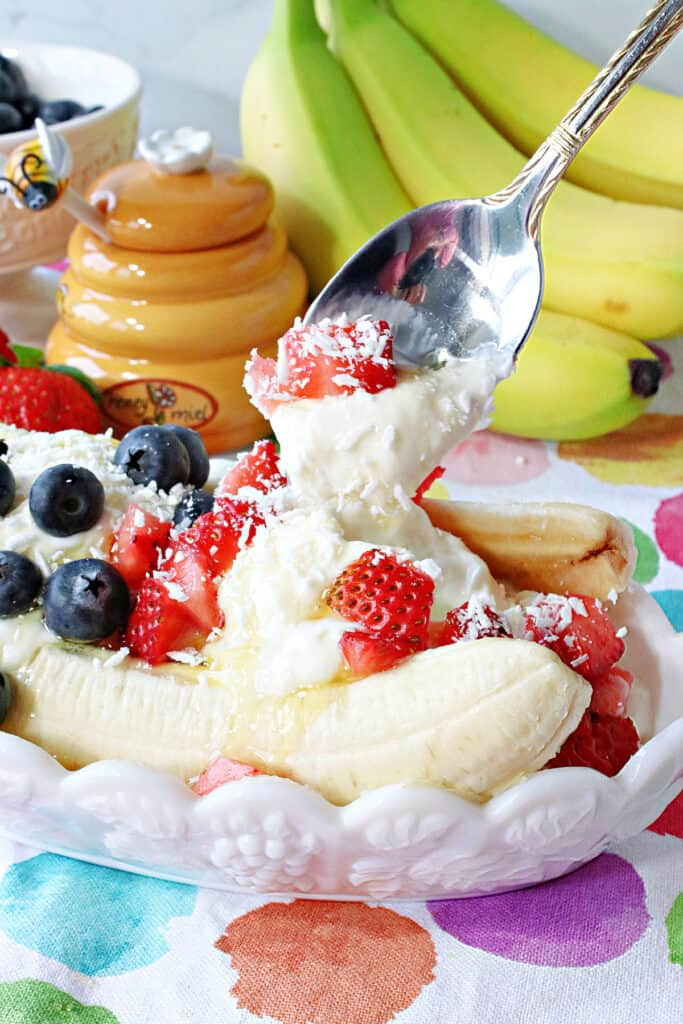 A vertical closeup of a spoon taking a scoop out of a Frozen Greek Yogurt Banana Split with fresh strawberries and blueberries on top.