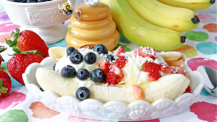A white banana split dish filled with a Frozen Greek Yogurt Banana Split with blueberries and strawberries on top.