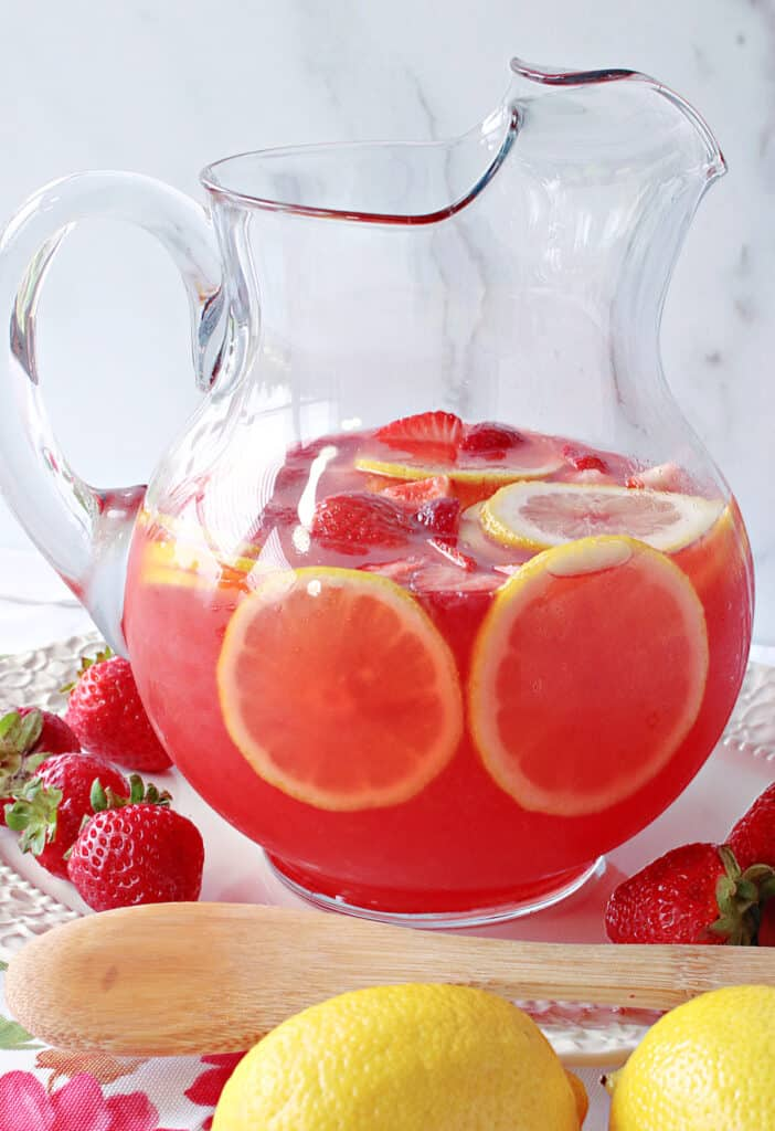 A vertical closeup of a pitcher filled with Lite Pink Lemonade with Strawberry Simple Syrup along with some fresh lemons, strawberries and a wooden spoon.