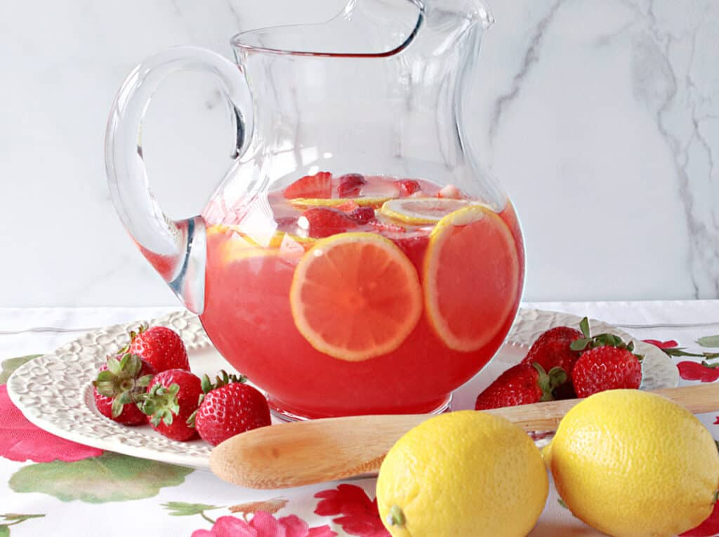 A horizontal photo of a glass pitcher filled with Lite Pink Lemonade with Strawberry Simple Syrup on a pretty platter with fresh lemons and strawberries on the platter.