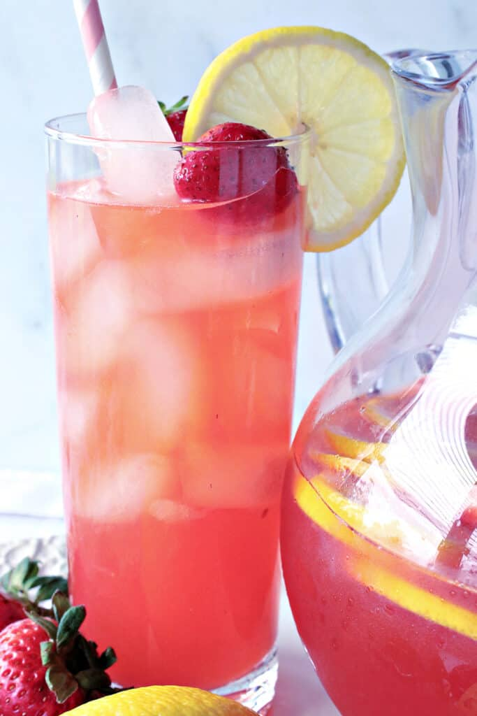 A closeup vertical photo of a tall glass of Lite Pink Lemonade with Strawberry Simple Syrup along with a lemon slice and a strawberry in the glass.