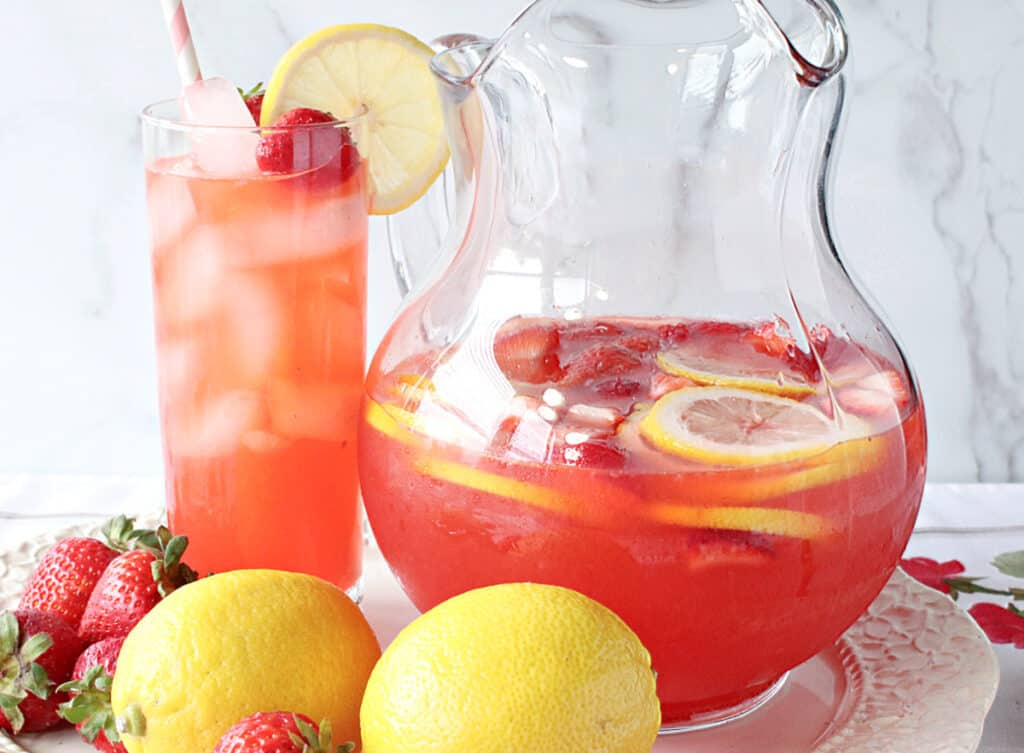 A horizontal photo of a glass and a glass pitcher filled with Lite Pink Lemonade with Strawberry Simple Syrup along with fresh lemons and strawberries in the photo as garnish.