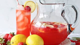 A glass and a pitcher filled with Lite Pink Lemonade with Strawberry Simple Syrup.