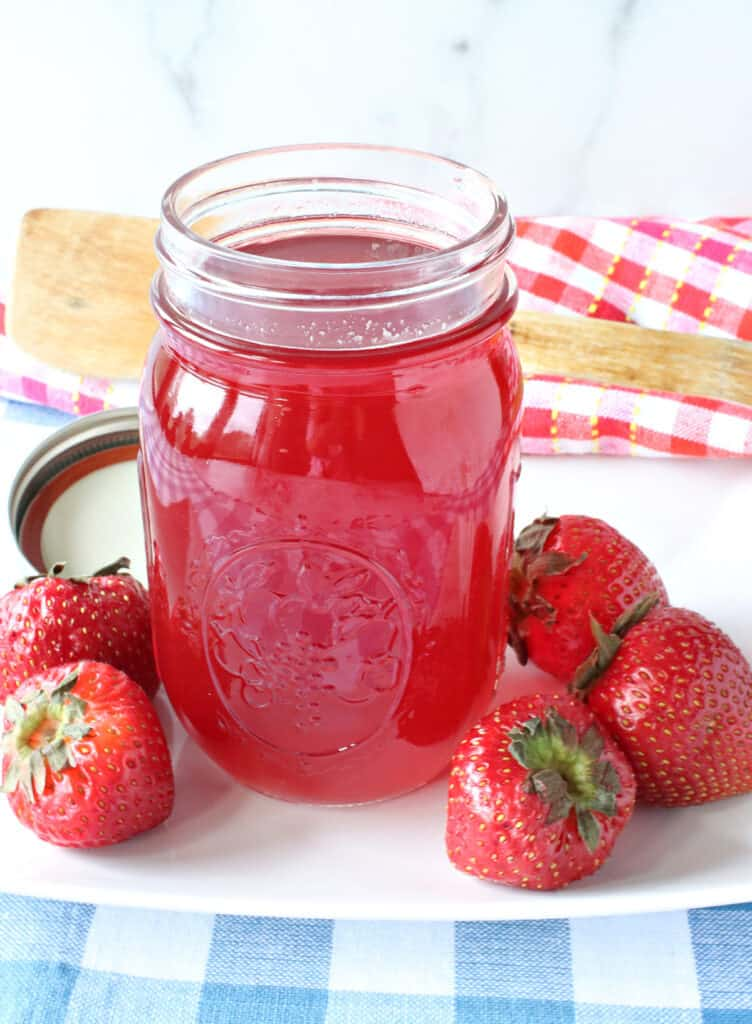 A mason jar filled with Lite Strawberry Simple Syrup made from monk fruit sweetener.