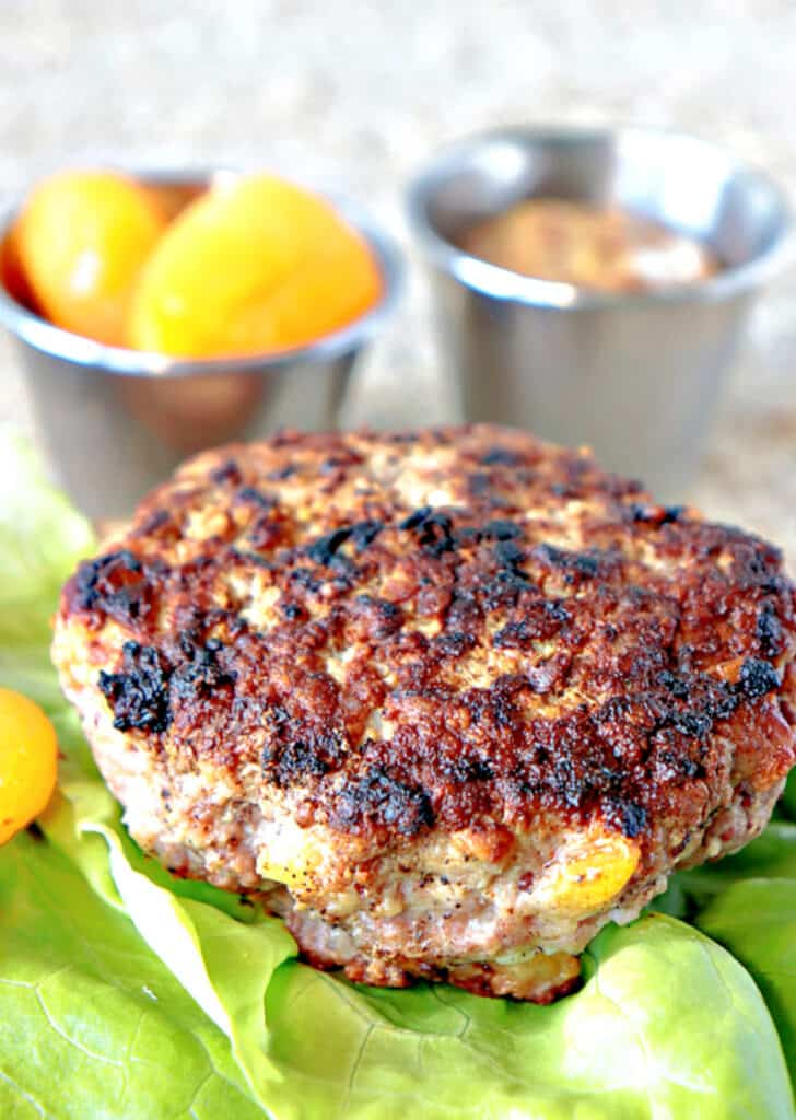 A closeup vertical image of a Pork Burger with Dried Apricots on a lettuce leaf along with two containers in the background with apricots and mustard.
