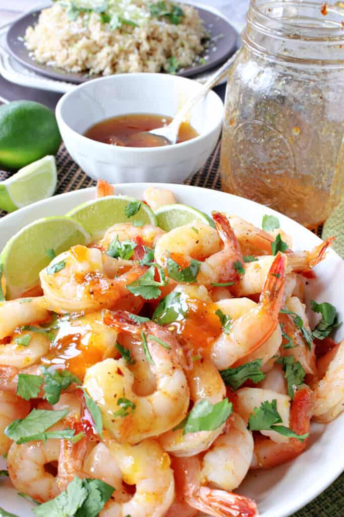 A vertical closeup photo of Whiskey Glazed Roasted Shrimp in a white bowl along with lime slices and cilantro.