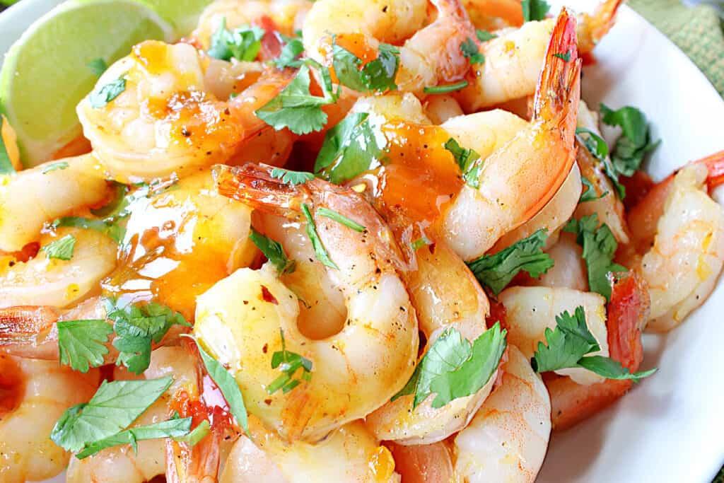A super closeup horizontal photo of Whiskey Glazed Roasted Shrimp with chopped cilantro and lime wedges.