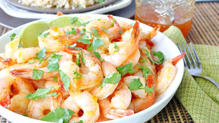 A white bowl filled with Whiskey Glazed Roasted Shrimp along with a jar of whiskey glaze in the background.