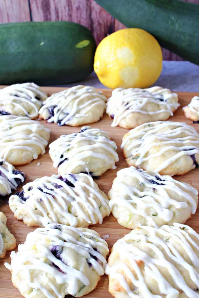 A closeup vertical photo of Zucchini Ricotta Cookies in the foreground along with a zucchini and lemon in the background.