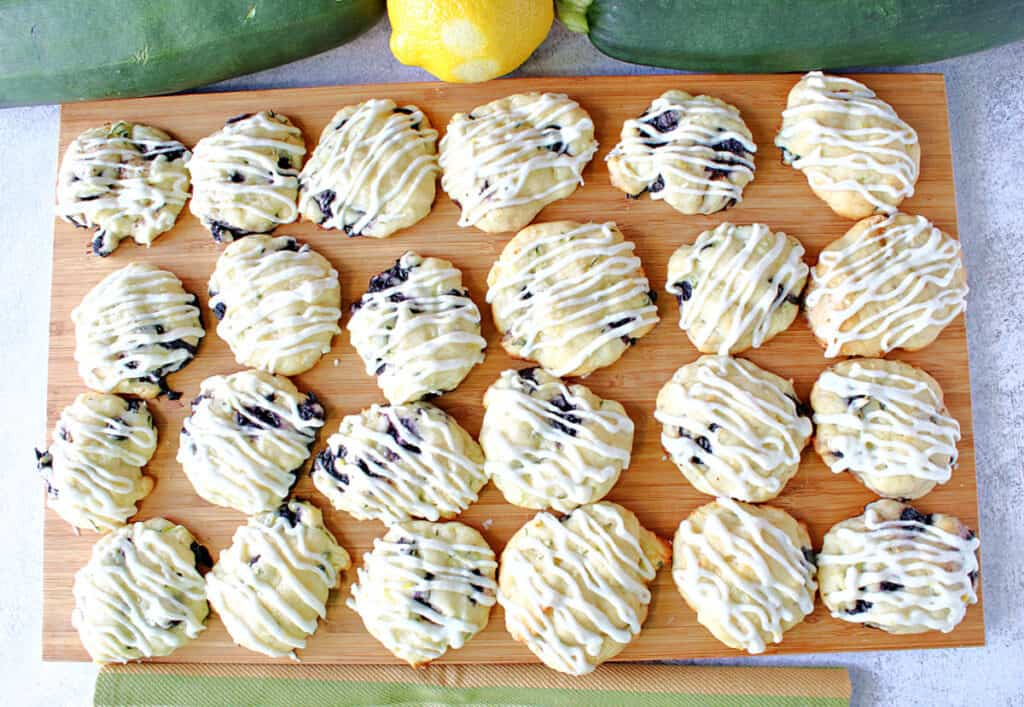 A directly overhead photo of a wooden tray filled with Zucchini Ricotta Cookies with a lemon buttercream icing drizzle.