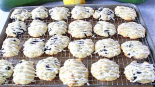 A baking sheet filled with Zucchini Ricotta Cookies that are drizzled with icing.