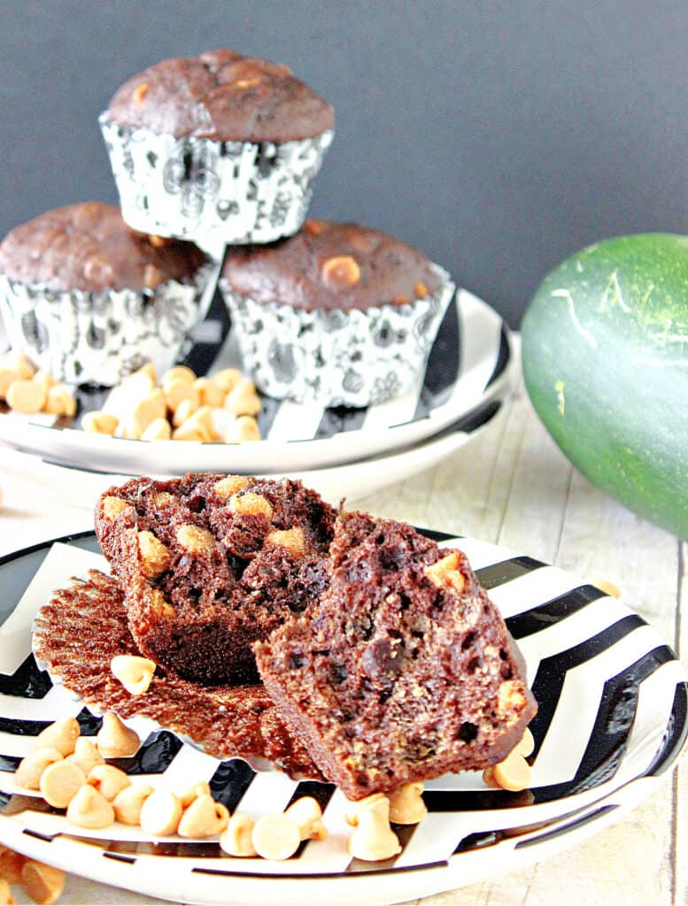 A closeup vertical photo of a Chocolate Zucchini Muffin with Peanut Butter on a black and white plate with a stack of muffins in the background.