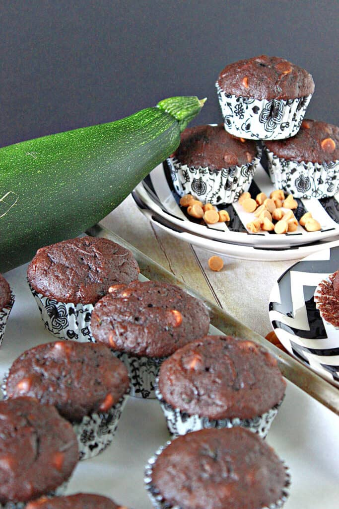 A vertical image of Chocolate Zucchini Muffins with Peanut Butter on a baking sheet in the foreground and a plate with muffins in the background.