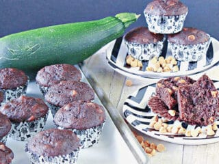 A tray of Chocolate Zucchini Muffins with Peanut Butter on the side along with a plate of muffins in the background.