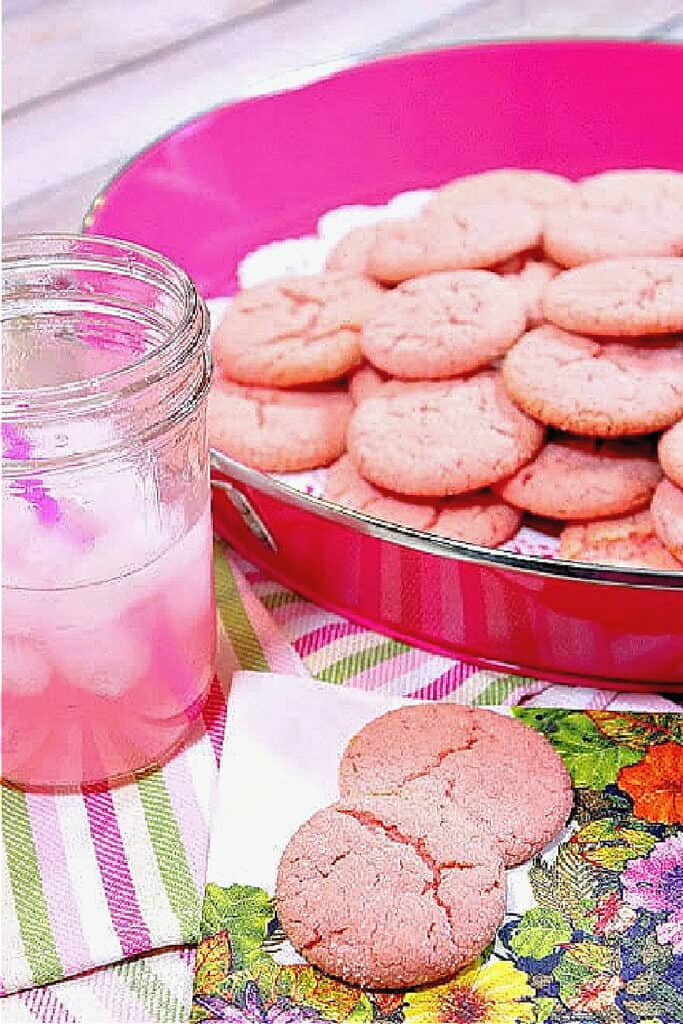 A pink tray filled with Pink Lemonade Cookies along with a glass of pink lemonade on the side with ice.