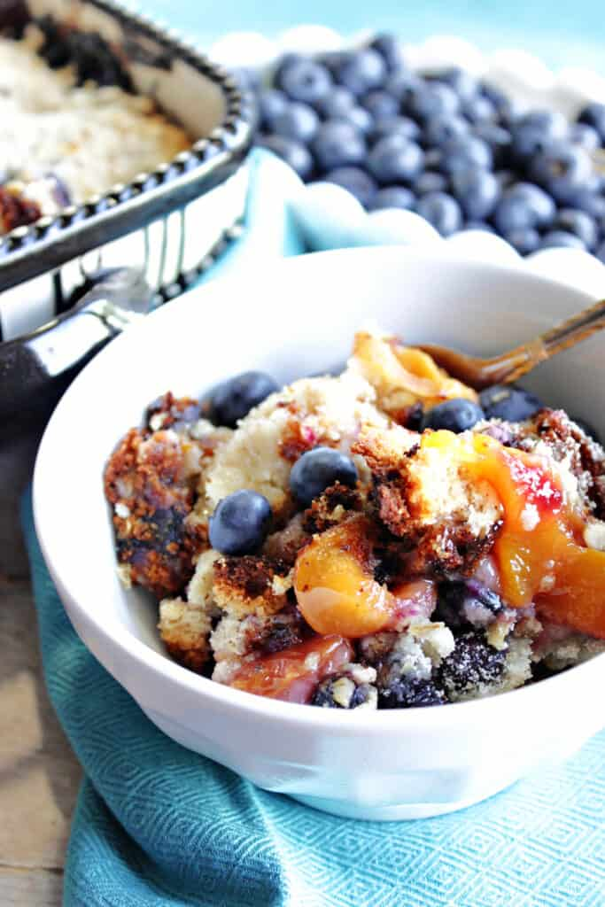 A vertical closeup photo of a serving of Blueberry Peach Crisp in a small white bowl with a blue napkin and a dish of fresh blueberries in the background.