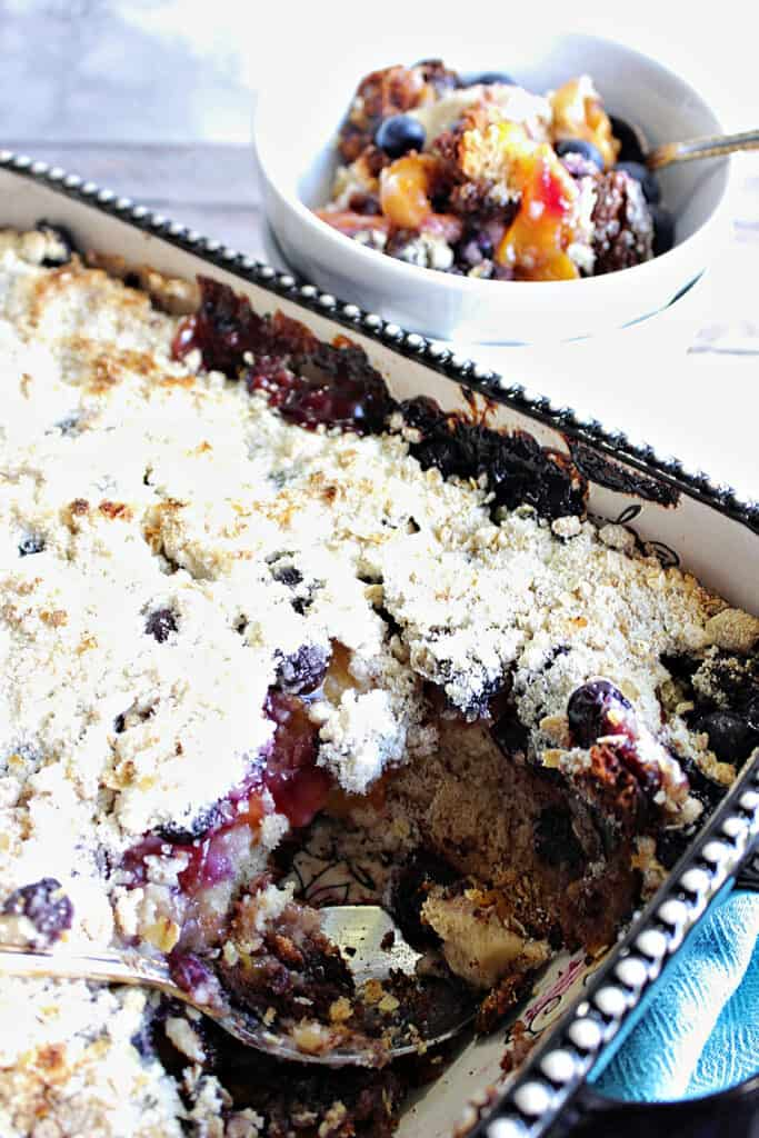 A vertical closeup of a rectangle baking dish filled with Blueberry Peach Crisp along with a small dish of crisp in the background.