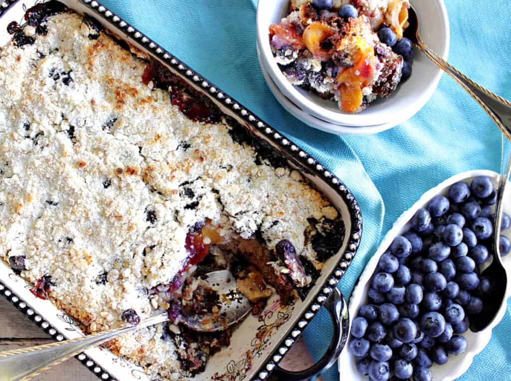 A direct overhead photo of a baking dish filled with Blueberry Peach Crisp along with a bowl of fresh blueberries and a few spoons.