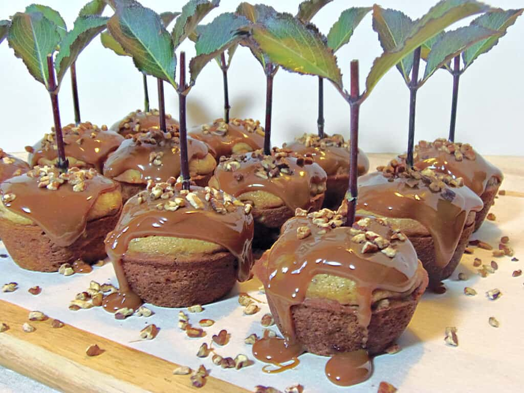 A lineup of Caramel Apple Cupcakes on a wooden board with dripping caramel, and chopped pecans.
