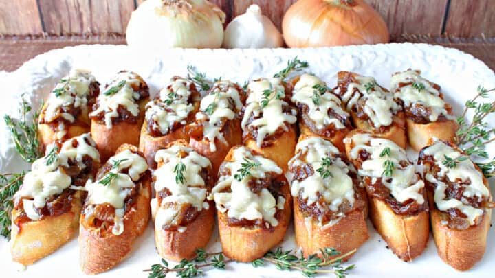 A horizontal photo of a white platter filled with French Onion Crostini with melted cheese and thyme sprigs on top.