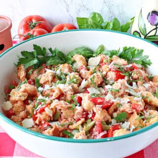 A large serving bowl filled with Italian Panzanella Salad topped with fresh basil and cheese.
