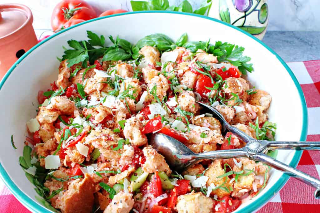 A horizontal closeup of an Italian Panzanella Salad in a large serving bowl with tongs, fresh basil, tomatoes, and Parmesan cheese.