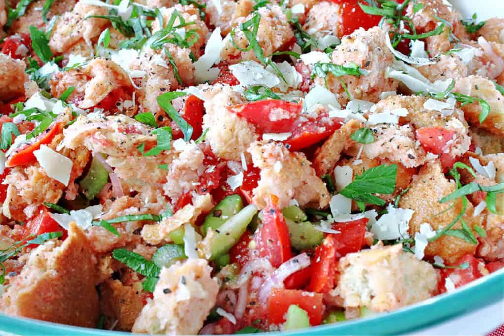 A closeup horizontal photo of an Italian Panzanella Salad topped with fresh tomatoes, fresh basil, and fresh Parmesan cheese.