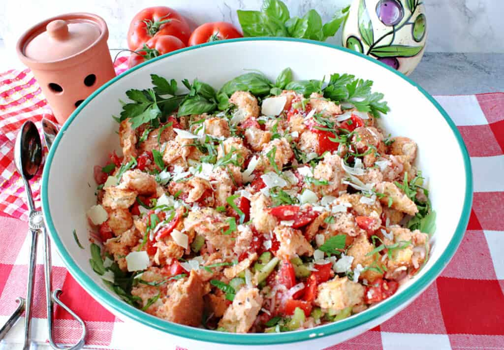 A horizontal closeup of a large bowl of Italian Panzanella Salad on a red and white tablecloth with salad tongs on the side.