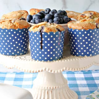 A white cake stand filled with some NY Times Blueberry Muffins in blue and white polka dot cups.