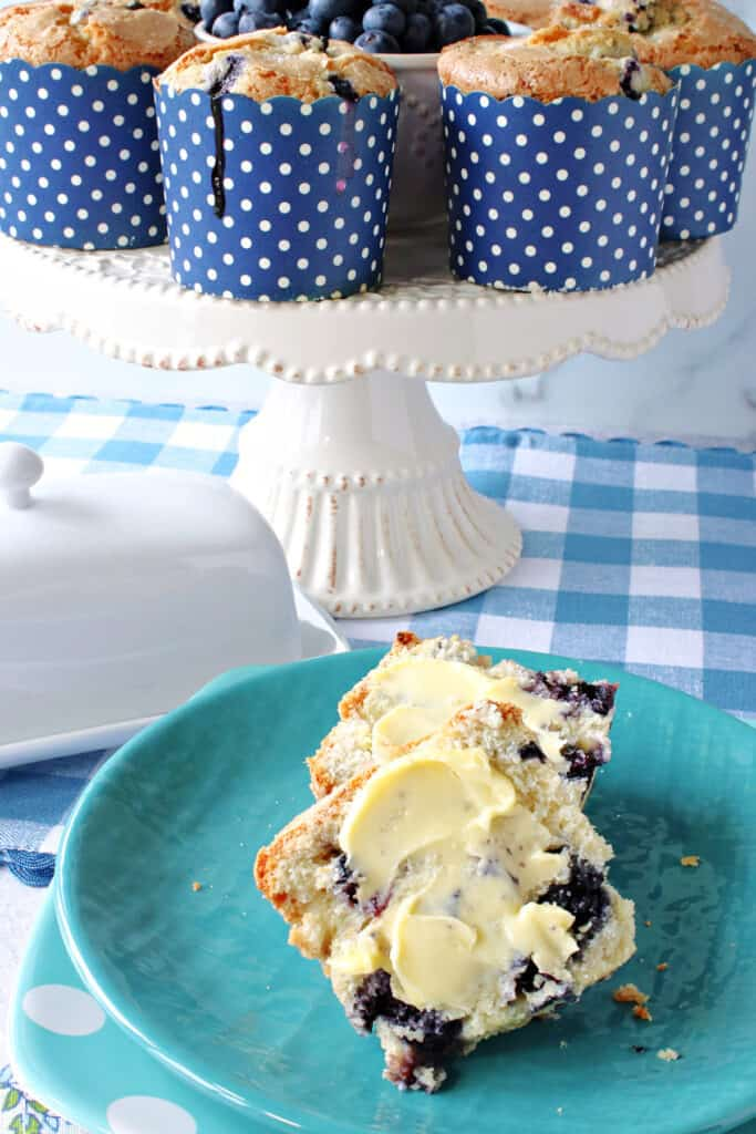 A vertical closeup of a NY Times Blueberry Muffin on a blue plate with butter along with a cake stand filled with muffins in the background.