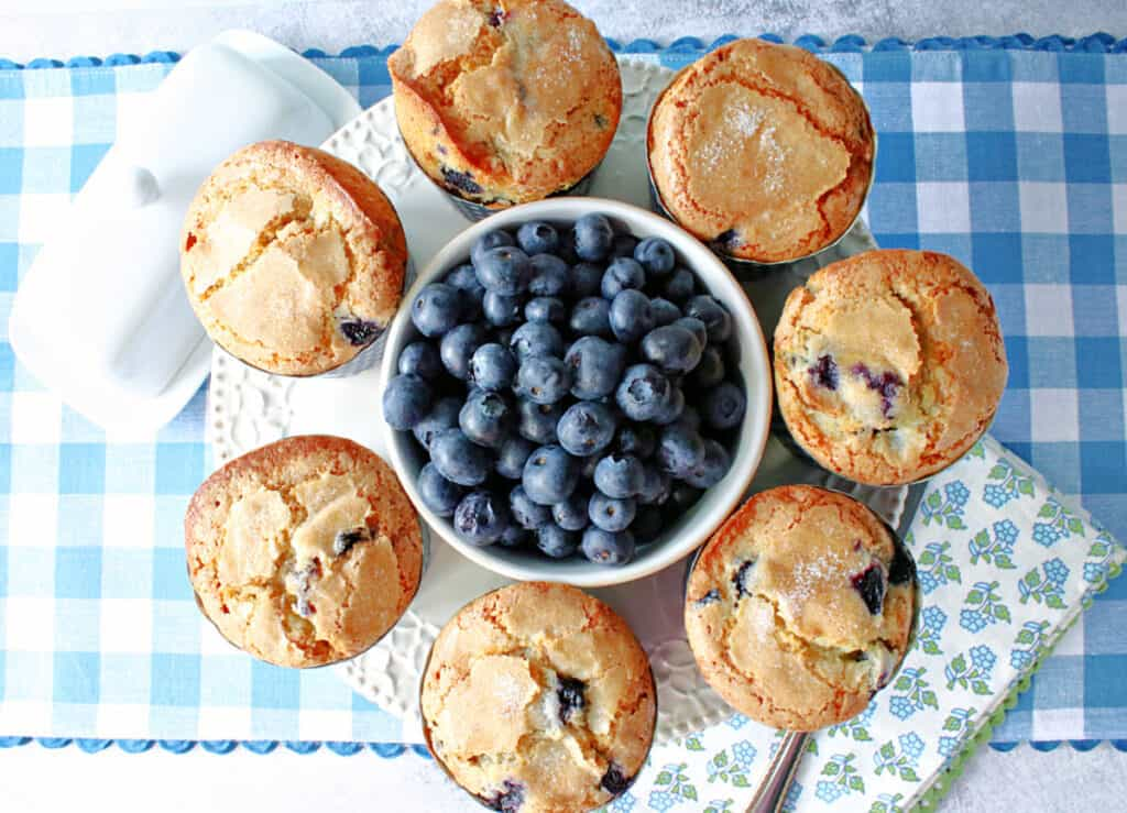 A direct overhead photo of a round cake plate filled with NY Times Blueberry Muffins along with a bowl of fresh blueberries in the center.