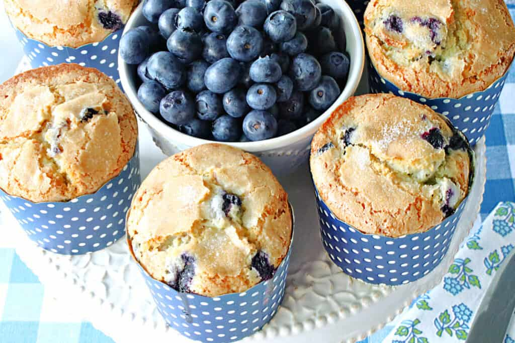 A horizontal overhead closeup photo of some NY Times Blueberry Muffins on a plate with fresh blueberries in the center and a blue and white checked napkin.