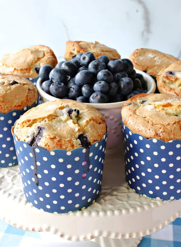 A closeup vertical photo of some NY Times Blueberry muffins on a cake stand with a bowl of fresh blueberries in the center.
